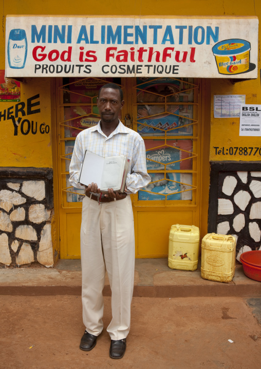 Rwandan man in front of a food shop mural, Kigali Province, Kigali, Rwanda