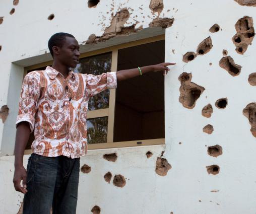 Rwandan man showing bullets holes in camp kigali memorial site, Kigali Province, Kigali, Rwanda