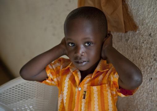 Rwandan child suffering from noise during a sunday mass in a church, Kigali Province, Kigali, Rwanda