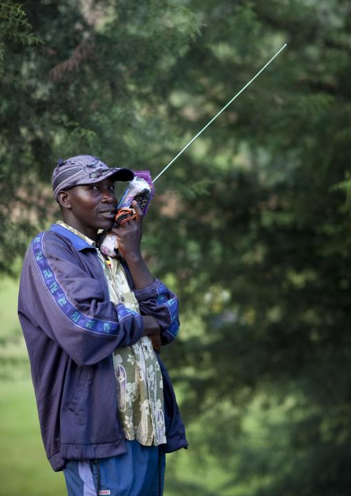 Man listening radio on road to rehengeri - rwanda