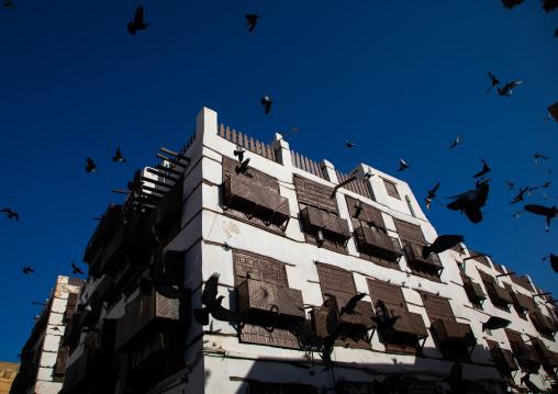 Pigeons flyiing over an old house with wooden mashrabiya in al-Balad quarter, Mecca province, Jeddah, Saudi Arabia