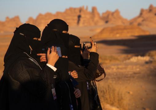 Saudi women in black niqabs taking pictures, Al Madinah Province, Alula, Saudi Arabia