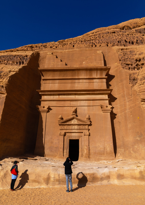 Tourists in front of a nabataean tomb in al-Hijr archaeological site in Madain Saleh, Al Madinah Province, Alula, Saudi Arabia