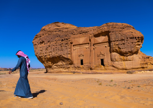 Saudi man walking in front of tombs in al-Hijr archaeological site in Madain Saleh, Al Madinah Province, Alula, Saudi Arabia