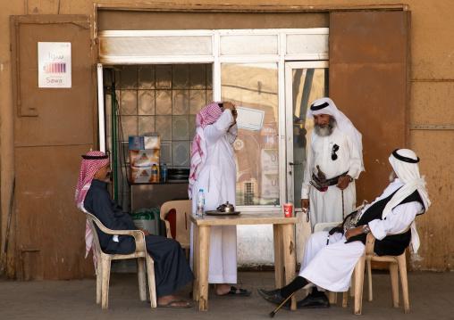 Saudi men drinking coffee in the market, Najran Province, Najran, Saudi Arabia