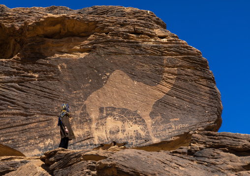 Tourist standing in front of a life-sized camel petroglyph on a rock, Najran Province, Thar, Saudi Arabia