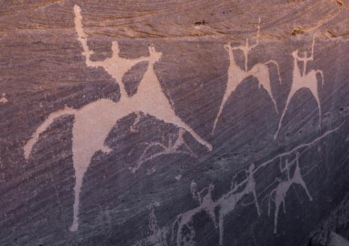 Petroglyphs on a rock depicting men hunting on horses, Najran Province, Minshaf, Saudi Arabia
