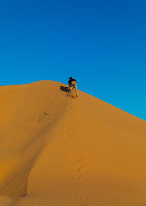 Tourist climbing a sand dune in the Rub' al Khali empty quarter desert, Najran province, Khubash, Saudi Arabia