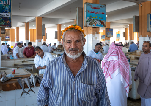 Saudi man with a flower garland i the fish market, Jizan Province, Jizan, Saudi Arabia