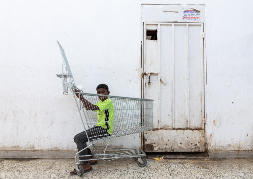 Boy playing with a shopping cart, Jizan Province, Jizan, Saudi Arabia