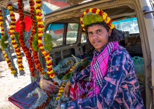 A flower vendor preparing floral garlands and crowns on a market in the back of his car, Jizan Province, Addayer, Saudi Arabia