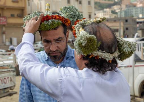 Portrait of a flower man offering a floral crown to a friend, Jizan Province, Addayer, Saudi Arabia