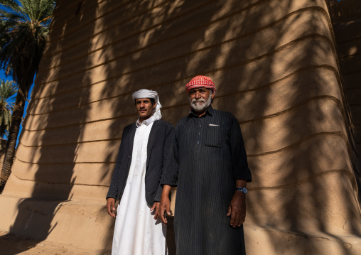 Saudi farmers standing in front of a traditional old mud house, Najran Province, Najran, Saudi Arabia