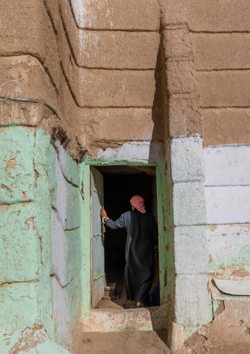 Saudi man entering in a traditional mud house, Najran Province, Najran, Saudi Arabia