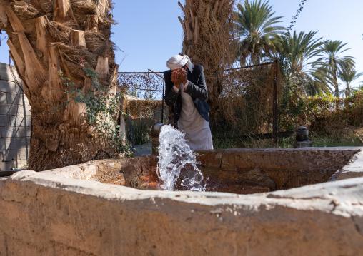 Thirsty saudi man drinking water in a farm well, Najran Province, Najran, Saudi Arabia