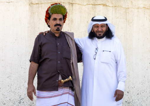 Portrait of a flower man wearing floral crowns on the head with a friend in traditional saudi clothing, Jizan Province, Addayer, Saudi Arabia