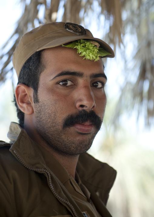 Policeman with basil under his cap to fight headache, Al-Jawf Province, Sakaka, Saudi Arabia