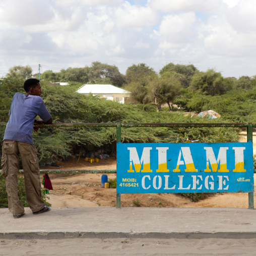 Standing man resting his elbow on a fence at miami college, Hargeisa, Somaliland