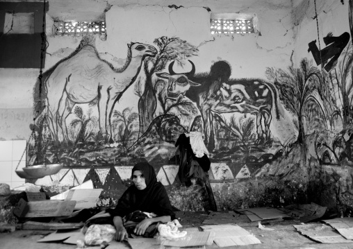 A woman sat on the floor in front of a livestock fresco, Hargeisa market, Somaliland
