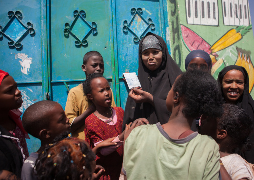 Somali girl discovering her picture on a polaroid, Woqooyi galbeed region, Hargeisa, Somaliland
