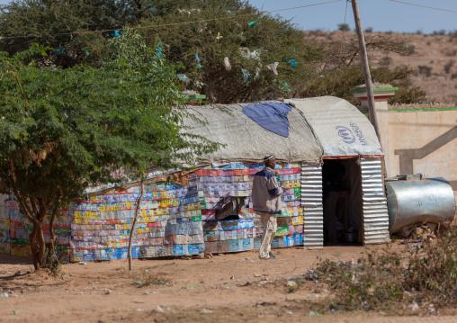 Somali man in front of a slum hut made of corrugated iron and canvas, Woqooyi galbeed region, Hargeisa, Somaliland