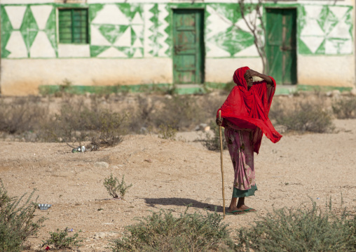 A senior woman wearing a bright red shawl and holding a stick looking at the horizon , Somaliland