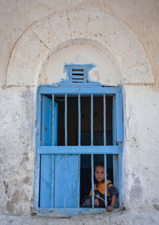 Young boy inside the window of a former ottoman empire house, Berbera area, Somaliland