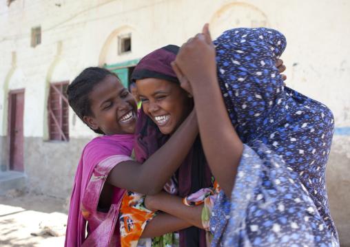 Three girls wearing colorful hijabs playing in a street, Berbera, Somaliland
