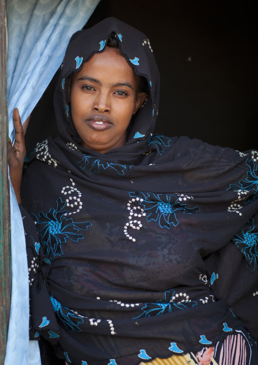 Portrait of a young woman wearing a purple shawl opening blue curtains, Somaliland