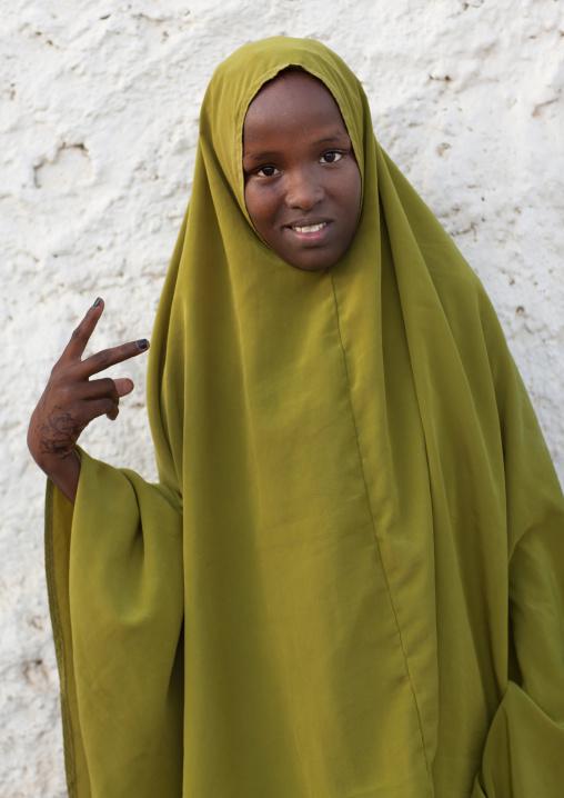 Portrait of a teenage girl in a khaki veil making v sign, Berbera, Somaliland