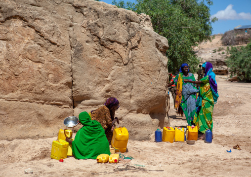Somali women taking drinking water from a well hole in the sand and pouring it into plastic containers, North-western province, Lasadacwo village, Somaliland