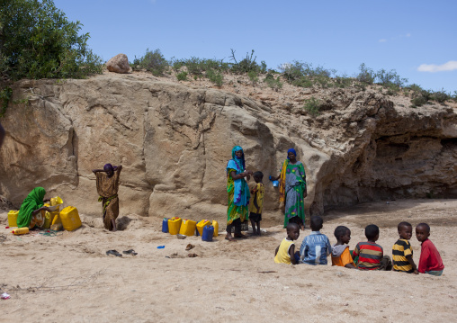 Women taking drinking water from a well hole in the sand and pouring it into containers children playing along, Lasadacwo village, Somaliland