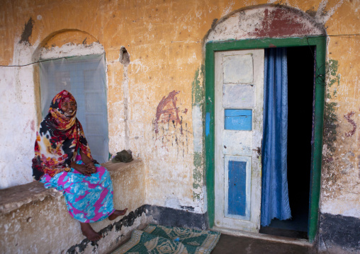 A woman wearing colorful patterned clothes in a former ottoman empire house, Berbera area, Somaliland