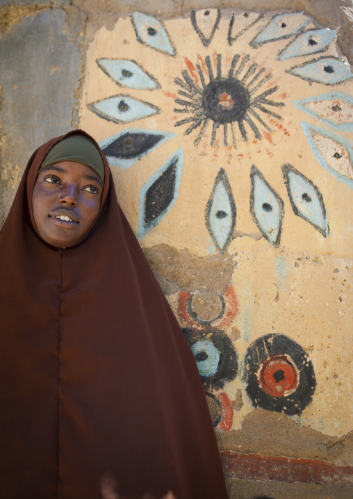 Young woman leaning against a painted wall, El sheikh, Somaliland