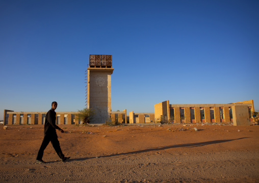 A man walking through the ruins of the burao technology institute at sunset, Burao, Somaliland