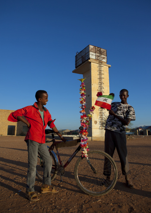 Two teenage boys outside the ruins of the burao technology institute holding a bike covered with plastic flowers and a somaliland flag, Burao, Somaliland