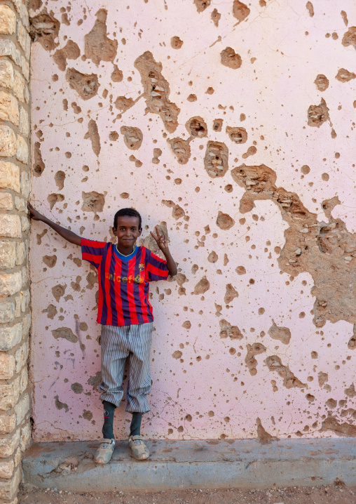 Somali boy with a barcelona football shirt in front of a wal full of bullets holes, Togdheer region, Burao, Somaliland