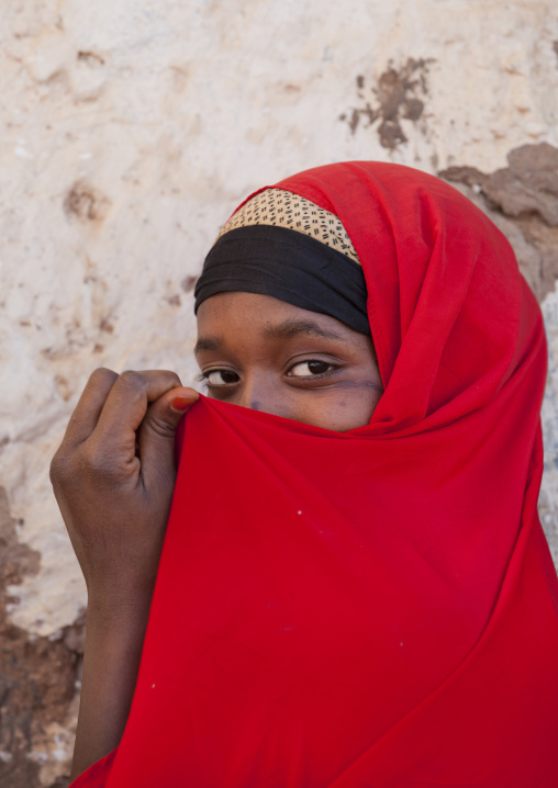 Portrait of a teenage girl wearing a red hijab hiding her mouth in her hijab, Baligubadle, Somaliland