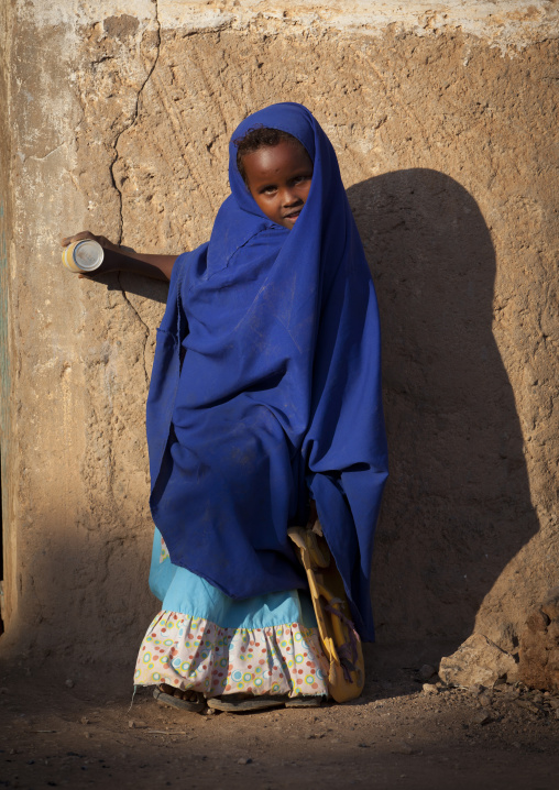 Little girl wearing a blue veil and holding a juice can leaning against a wall, Baligubadle, Somaliland