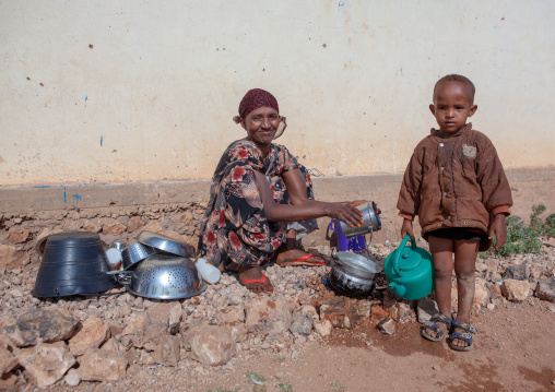Somali mother with her son washing kitchen tools outside of her home, Woqooyi galbeed province, Baligubadle, Somaliland