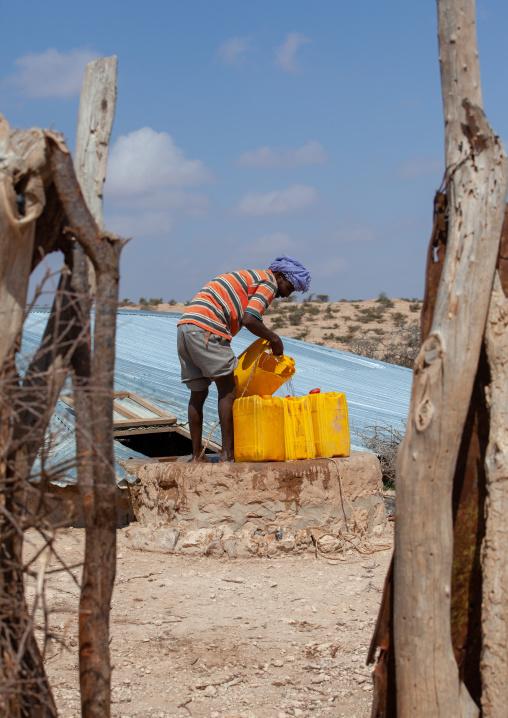 Somali man collecting water in a well, Dhagaxbuur region, Degehabur, Somaliland