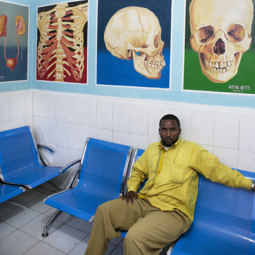 A man in a waiting room with organs depicted onto the wall, Hargeisa, Somaliland