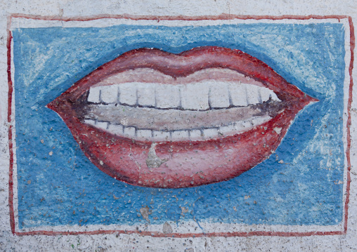 Dentist advertisement painted sign showing mouth and teeth on a blue background, Boorama, Somaliland