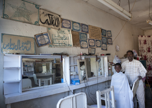 Interior of barber shop with a young boy in a while shawl getting a hair cut by an adult hairdresser, Boorama, Somaliland
