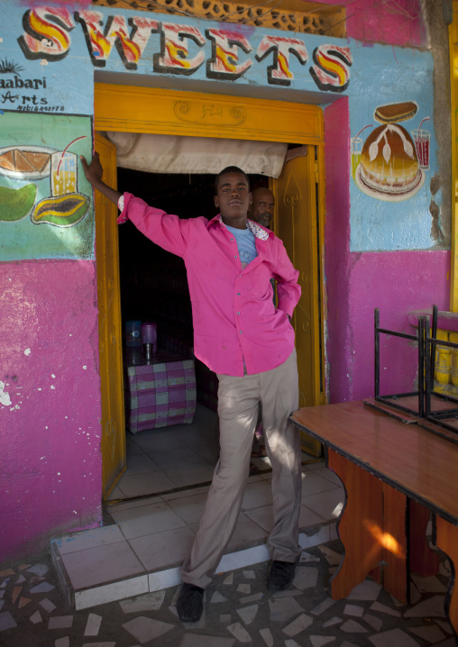 A young man wearing a pink shirt standing in the door frame of a sweets shop, Boorama, Somaliland