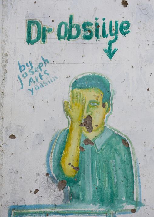 An optician advertisement painted billboard depicting a man taking an eye test, Boorama, Somaliland