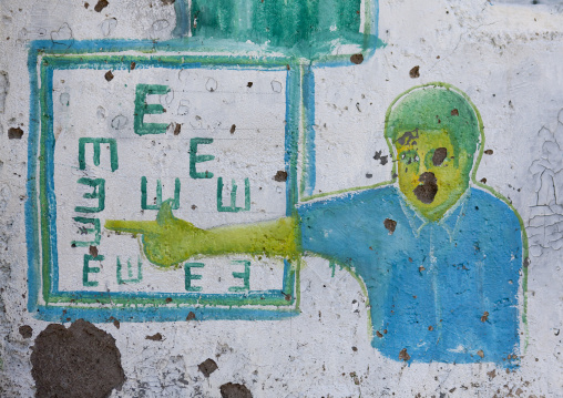 An optician advertisement painted billboard depicting an optician giving an eye test, Boorama, Somaliland