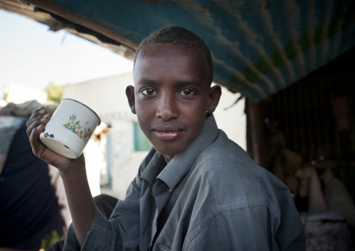Portrait of a boy holding an enamel mug and wearing a blue shirt, Boorama, Somaliland
