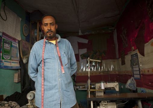 A tailor wearing a blue shirt and tape measure on his neck in his workshop, Boorama, Somaliland
