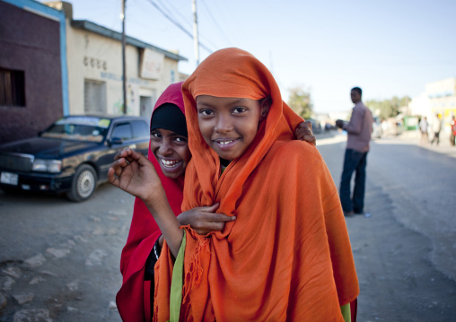 Two teenage girls wearing orange and red hijabs laughing at the camera on a street, Boorama, Somaliland